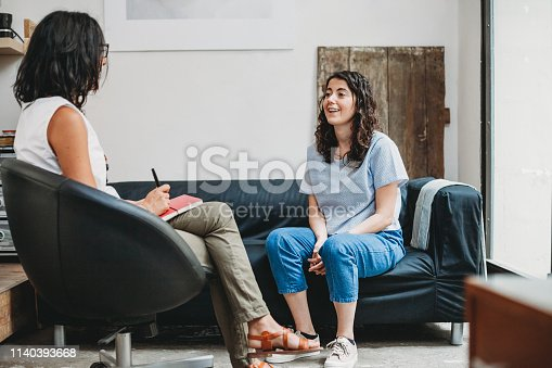 Psychotherapy session, woman talking to his psychologist in the studio