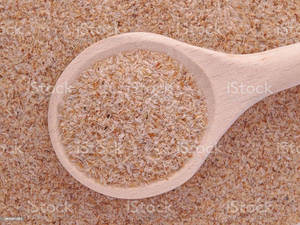 Psyllium seeds husks in wooden spoon stock photo