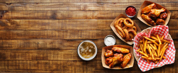 pub appetizers such as chicken wings, onion rings and french fries in panoramic composition stock photo