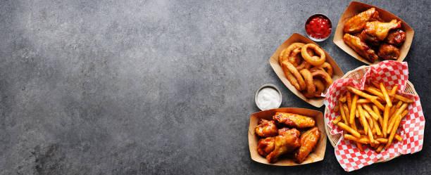 pub voorgerechten zoals kippenvleugels, uienringen en frietjes in een panoramische compositie foto