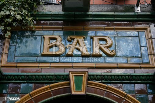 Glazed tile, three-dimensional lettering of the word 'Bar', in antique Art Nouveau style on the exterior fascia of a British Pub