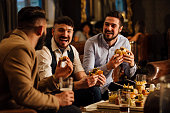 Three men are sitting together in a bar/restaurant lounge. They are laughing and talkig while enjoying burgers and beer.