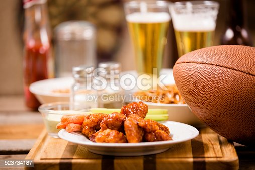 Sports bar, pub setting. Spicy chicken wings foreground. Football, pretzels, peanuts, beer on bar counter top. Dartboard in background.