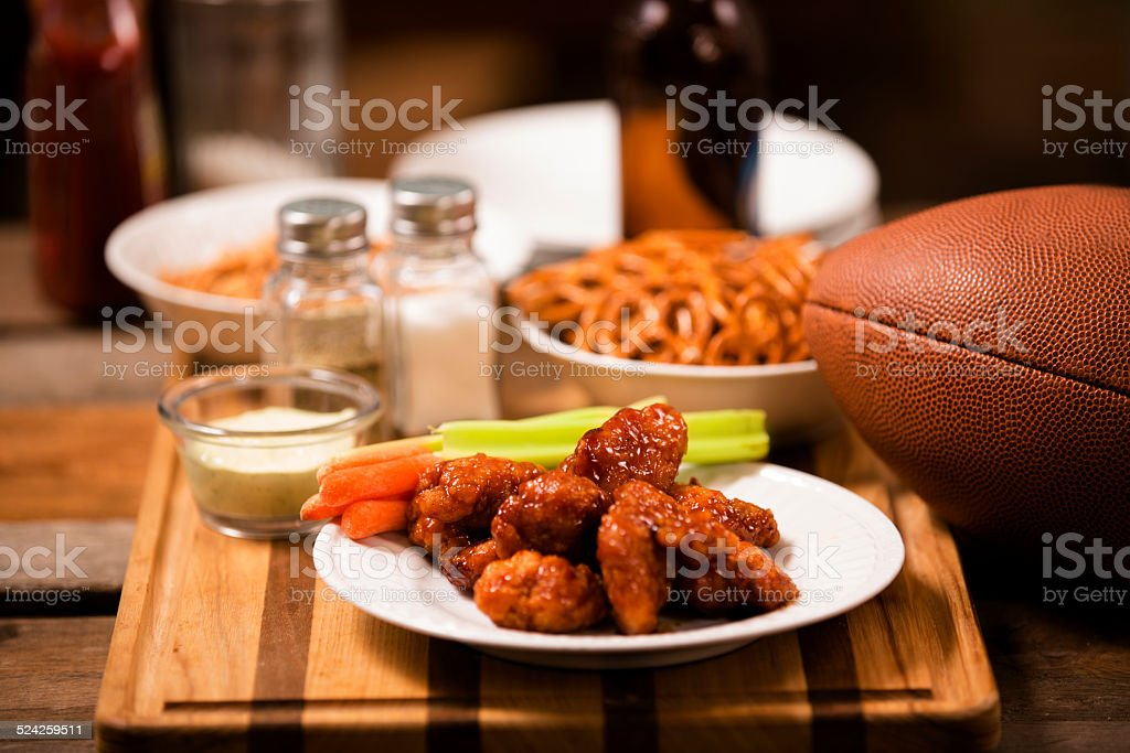 Pub food. Snacks, beer, football. Spicy chicken wings. stock photo