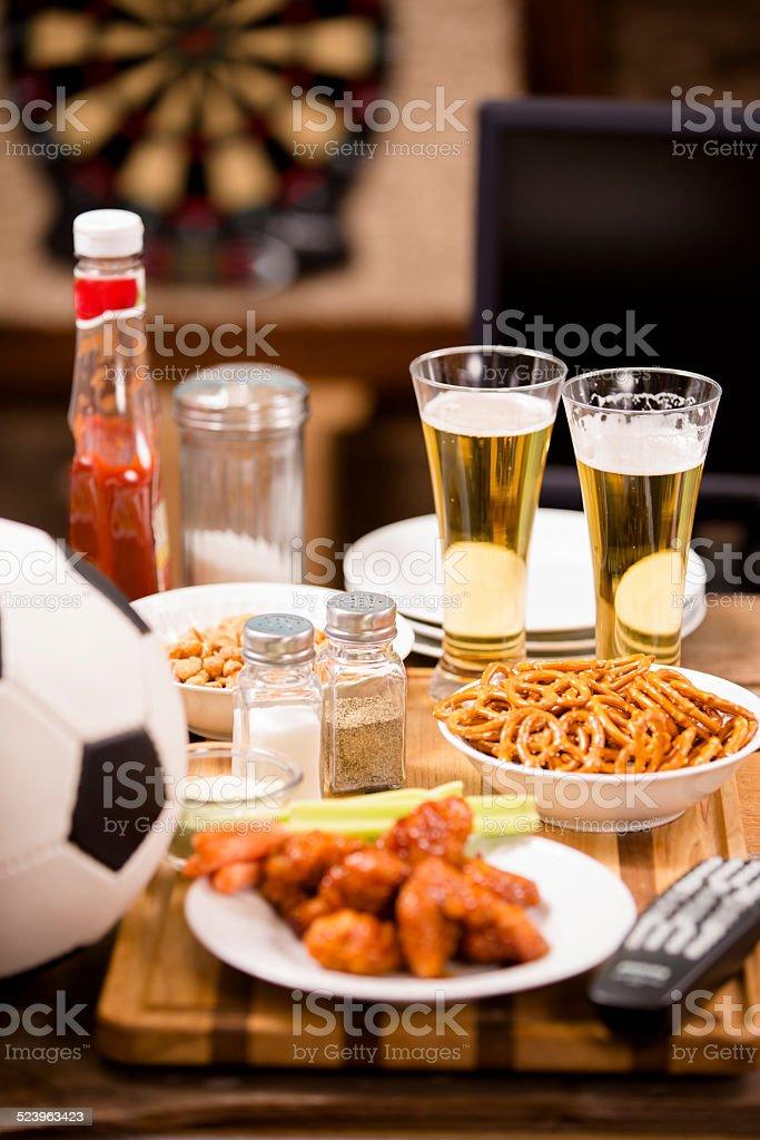 Des plats de Pub. Des en-cas, bière, ballon de football. Des ailes de poulet épicées. - Photo