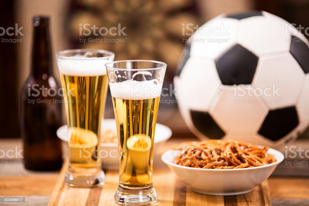 Sports bar, pub setting. Soccer ball, pretzels, beer on bar counter...