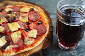 Pub or pizzeria concept. Delicious pizza and mug of dark beer, close up