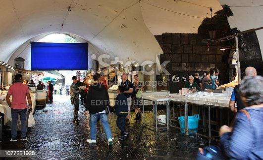 Catania, Italy - 2nd December 2018: Vendors selling fish and various people walking and standing at the pubic fish market of Catania