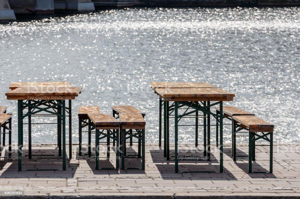 öffentliche Bier Garten alte Vintage Stühle und Sitzbänke, Tische im sonnigen Tag in der Nähe von Wasser – Foto