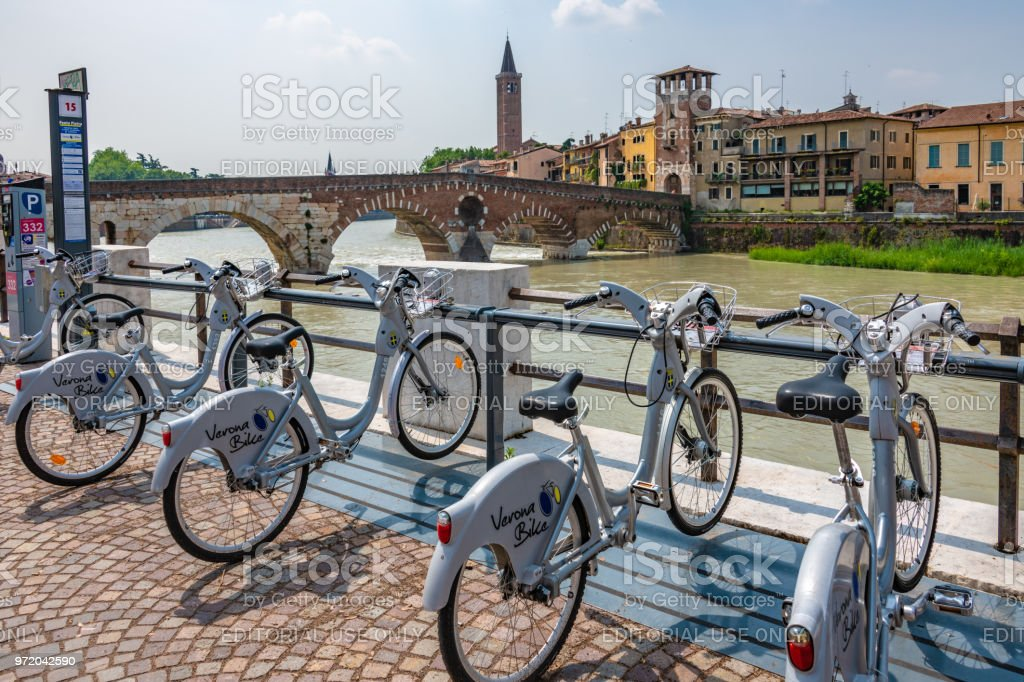 Public bicycle hire by the river in Verona, Italy stock photo