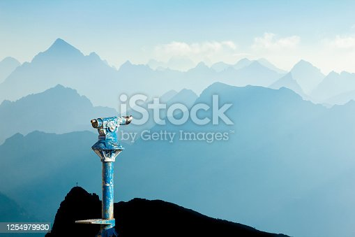 Public binoculars provide far view to distant blue mountain ranges silhouette in early Morning Sunlight. Foresight and vision for new and creative business concept and ideas. Alps, Allgau, Bavaria, Germany.