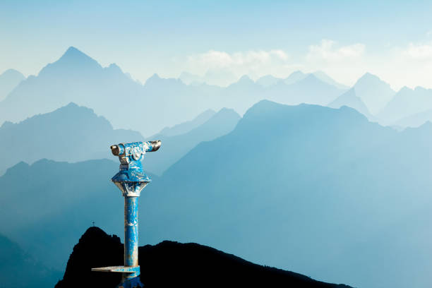 Public binoculars and Mountain Silhouettes at Sunrise. Foresight and vision for new business concepts and creative ideas. Alps, Allgau, Bavaria, Germany. Public binoculars provide far view to distant blue mountain ranges silhouette in early Morning Sunlight. Foresight and vision for new and creative business concept and ideas. Alps, Allgau, Bavaria, Germany. the way forward stock pictures, royalty-free photos & images