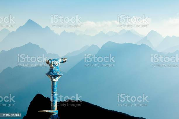 Photo of Public binoculars and Mountain Silhouettes at Sunrise. Foresight and vision for new business concepts and creative ideas. Alps, Allgau, Bavaria, Germany.