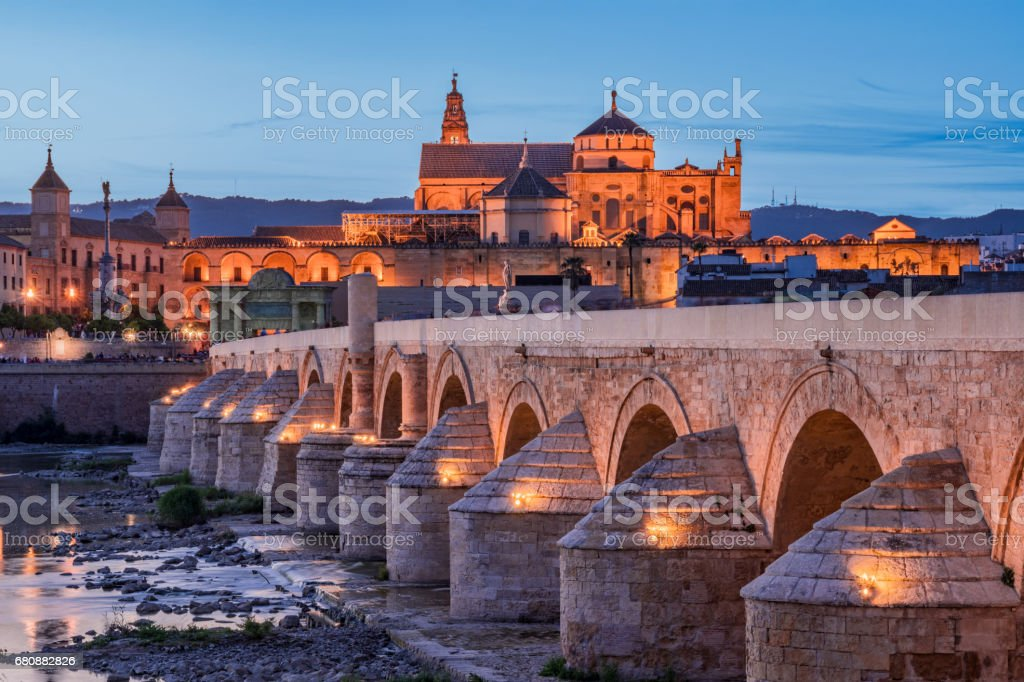 Public Bridge On The River At Dusk With Mosque In The Background In Cordoba Andalusia Spain stock photo