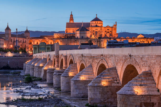 Public Bridge On The River At Dusk With Mosque In The Background In Cordoba Andalusia Spain Bridge With Reflections In Water cordoba mosque stock pictures, royalty-free photos & images