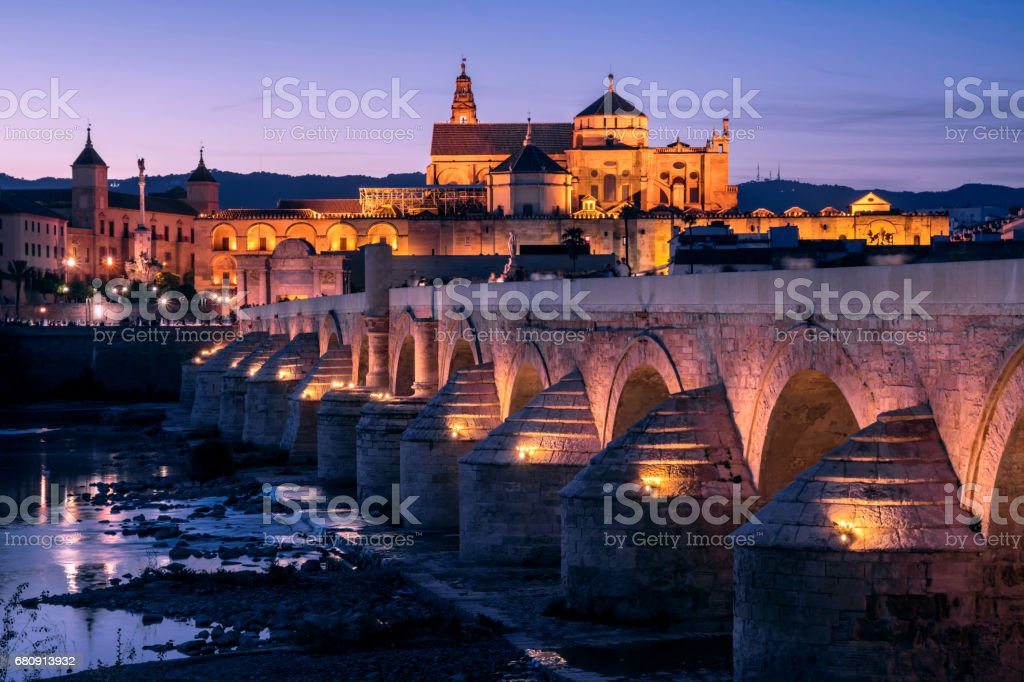 Public Bridge On The River At Dusk With Mosque In The Background In Cordoba Andalusia Spain royalty-free stock photo