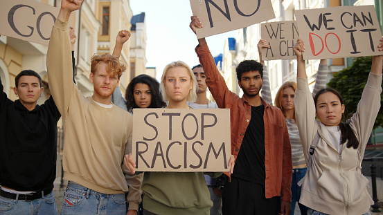 Public demonstration at street against racism with slogans on posters. Multiethnic people protest