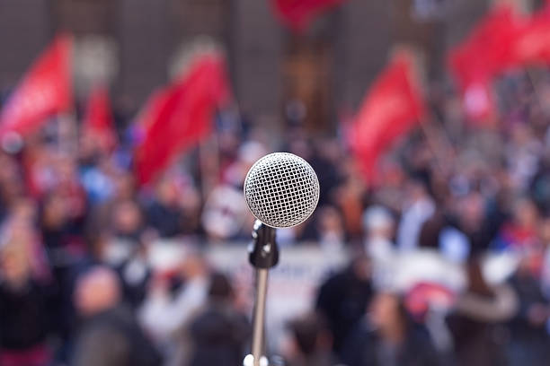 Public demonstration. Protest. Microphone in focus against unrecognizable crowd activist stock pictures, royalty-free photos & images