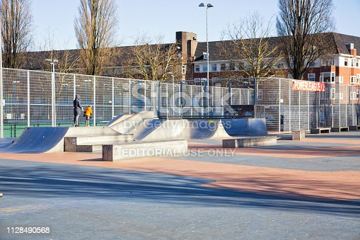 Amsterdam, The Netherlands - November 2018. Mother and son in fenced outdoor skatepark with various ramps on a winter sunny day in Amsterdam, The Netherlands.