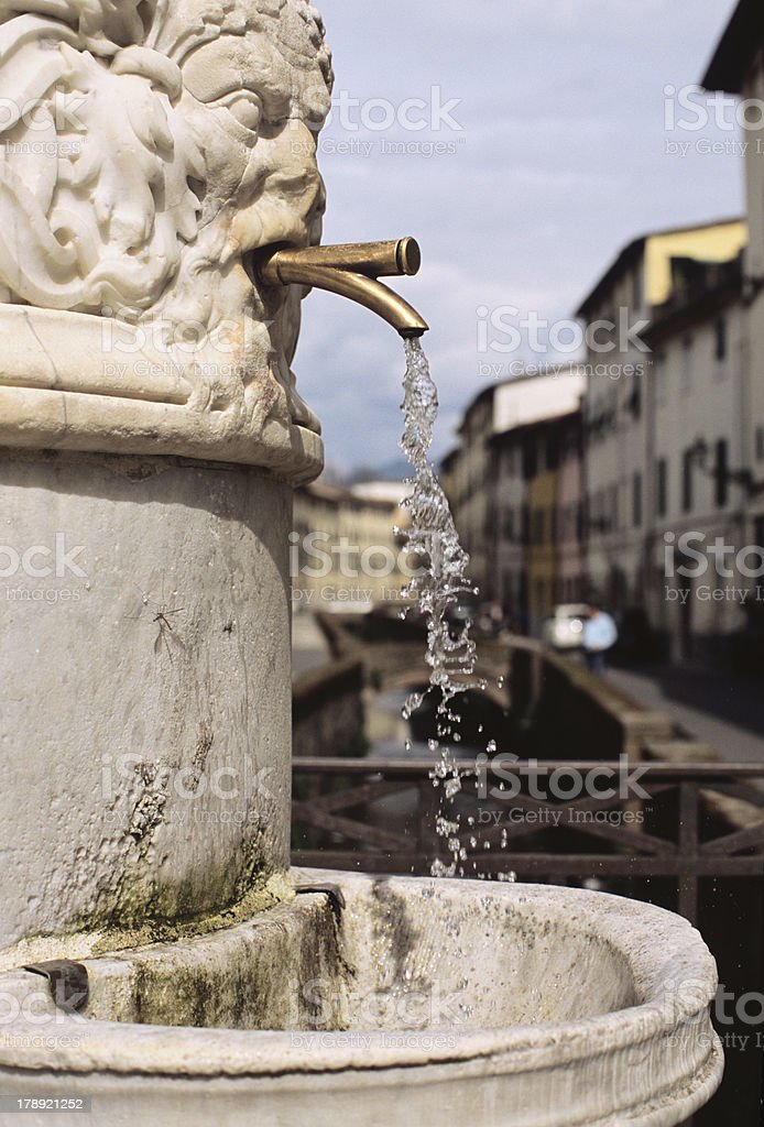 Public fountain in Lucca, Tuscany, with view of a canal royalty-free stock photo