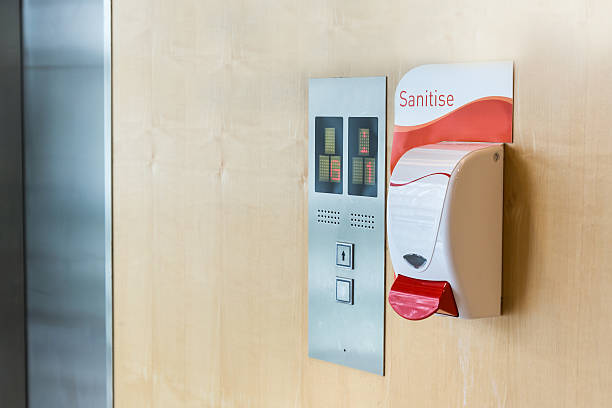 public hand sanitizer next to elevator - hand sanitizer fotografías e imágenes de stock