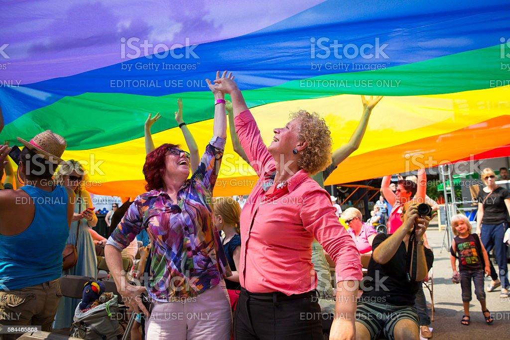 public having fun under a rainbow flag, Amsterdam Gay EuroPride stock photo