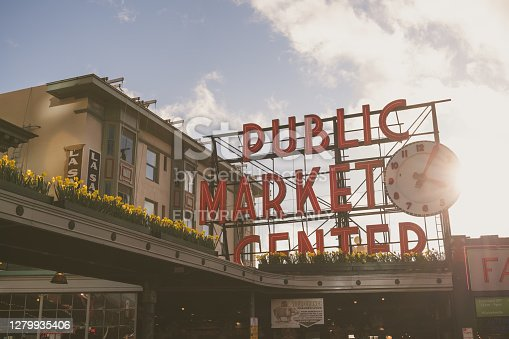 Seattle, USA - Feb 23, 2020: The iconic illuminated public market sign at Pike Place on Pine street late in the day with sun-flare.