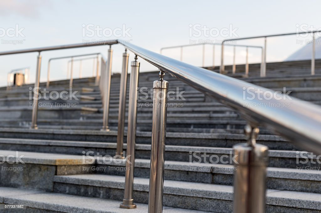 Public metal chrome handrail on gray staircase at city stock photo