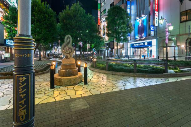 夜のサンシャインストリートの高音のクレフで形作られた公共の記念碑。 - モニュメント池袋 ストックフォトと画像