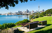 Wooden Benches in Waterfront Park (near harbor), with a view of  Auckland's modern skyline- Auckland, New Zealand