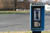 Front view of a pay phone next to an empty rural road.