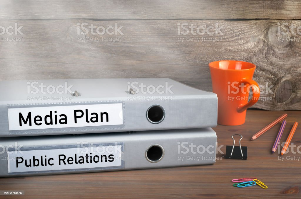 Public Relations and Media Plan - two folders on wooden office desk stock photo