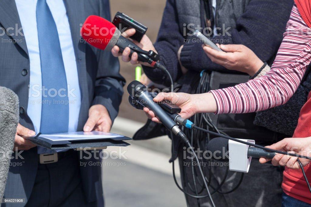 Media interview. Broadcast journalism. Microphones.
