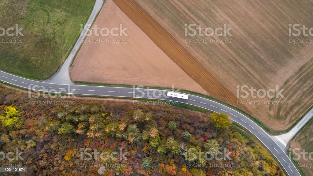 Public service vehicle driving on country road through agricultural...