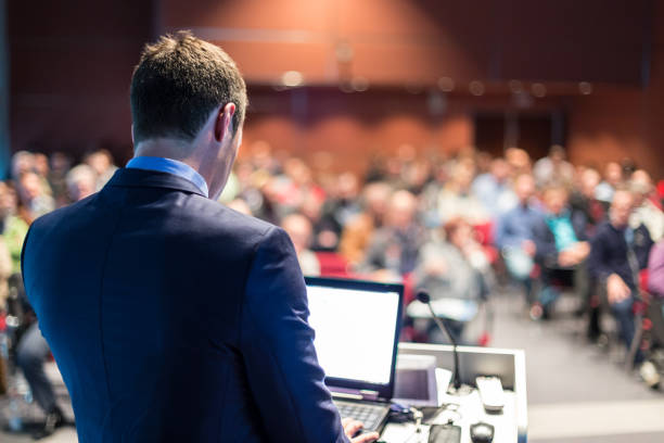 Public speaker giving talk at business event. Speaker giving a talk on corporate business conference. Unrecognizable people in audience at conference hall. Business and Entrepreneurship event. speech stock pictures, royalty-free photos & images
