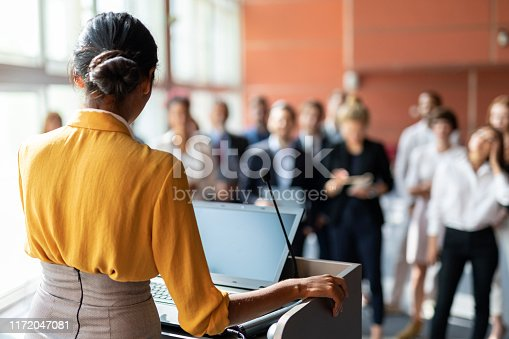 An Indian female presenter at a conference, audience in the background