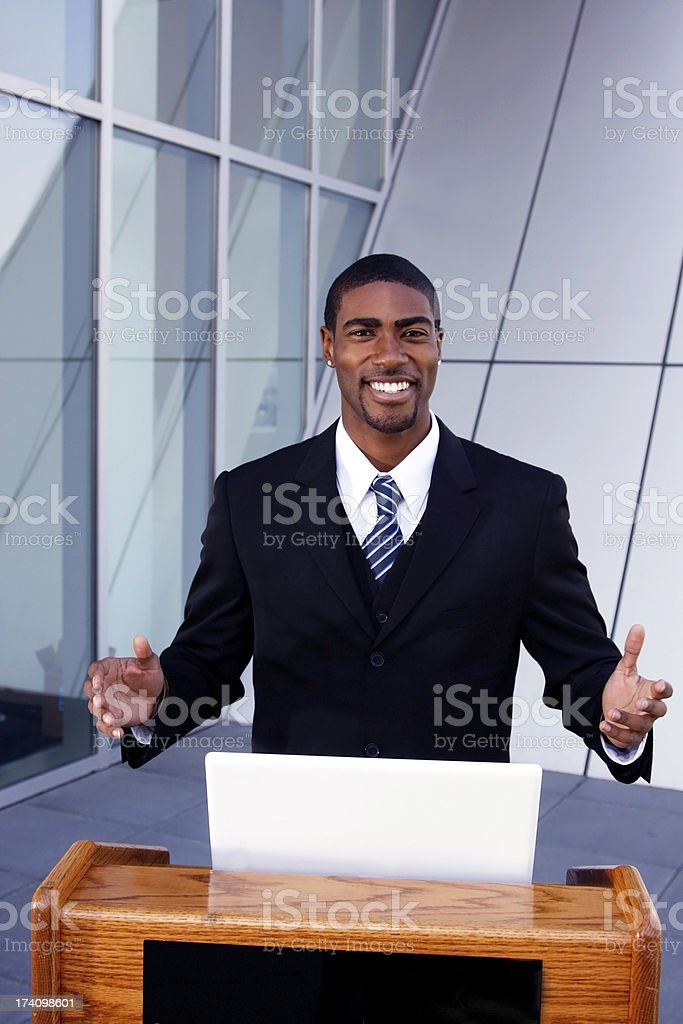 A public speaker wearing a black coat and tie  stock photo