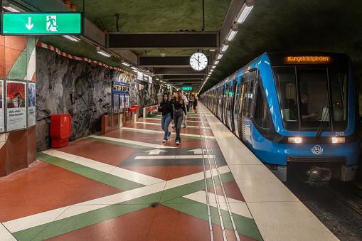 Stockholm, Sweden - July 20, 2021: Perspective view of SL public subway train entering the decorative station Kungsträdgården with incidental people in Stockholm Sweden July 20, 2021.
