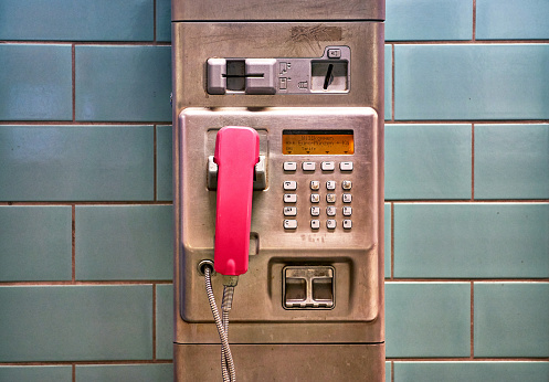 Public telephone made of silver metal with pink telephone receiver.