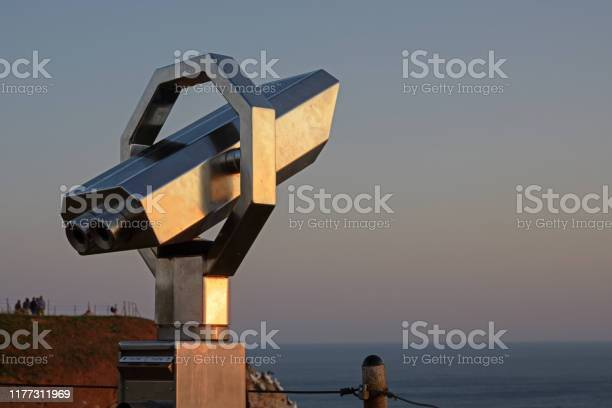 Photo of Public telescope to watch the birds at a vantage point on the cliffs of Heligoland during sunset, copy space