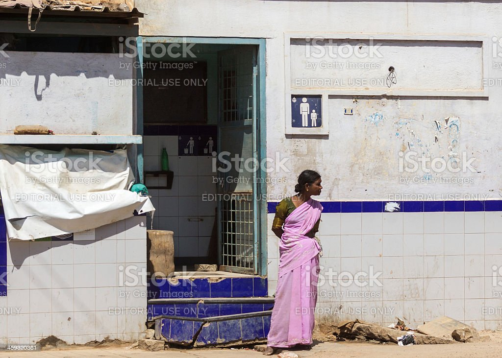 Public toilet for men in Bangalore. BENGALURU, INDIA - OCTOBER 5, 2013: Female responsible guards the entrance to the trashed toilet. Adult Stock Photo