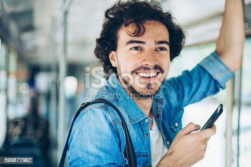 Young man with smart phone traveling in public transport.