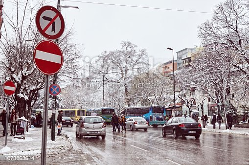Public transport in a snowy winter day. Bus station at the main street of Bursa city 'Ataturk caddesi' in a snowy winter day