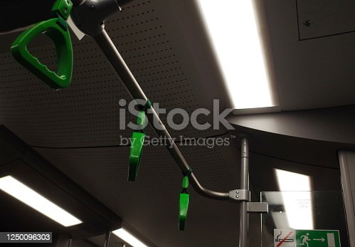Green hanging hand-rail in public transport.