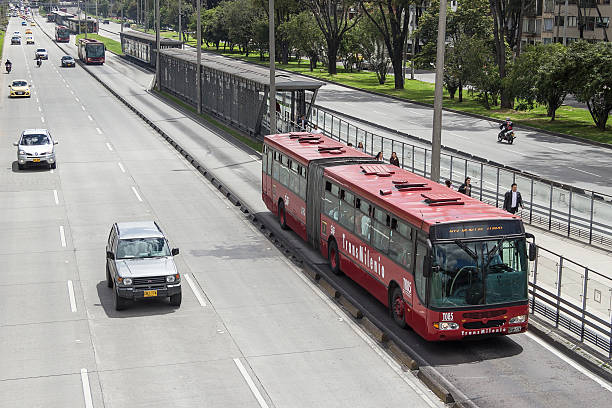 """Public transport system at Bogota. Bogota, Colombia- May 5, 2016: Articulate bus car and station at 85th st of the massive transport system known as """"transmilenio"""" at Bogota, Colombia. bus rapid transit stock pictures, royalty-free photos & images"""