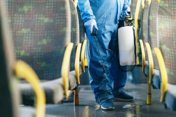 Public transportation healthcare. Man in protection suit disinfecting the bus interior, during COVID-19. Everything will be fine.