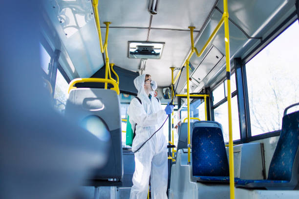 public transportation healthcare. man in white protection suit disinfecting and sanitizing handlebars and bus interior to stop spreading highly contagious coronavirus or covid-19. - tuta protettiva foto e immagini stock