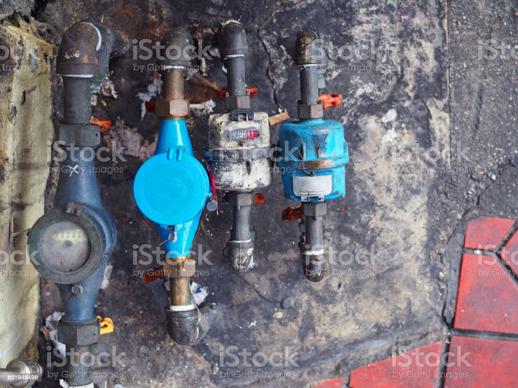Public water meter and piping, old dirty stained stock photo