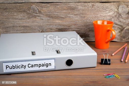 842214626istockphoto Publicity Campaign. Folder, Coffee Mug, colored pencils on wooden office desk 813320086