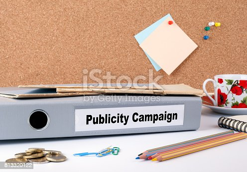 842214626 istock photo Publicity Campaign. Folder on office desk. Money, Coffee Mug and colored pencils 813320122